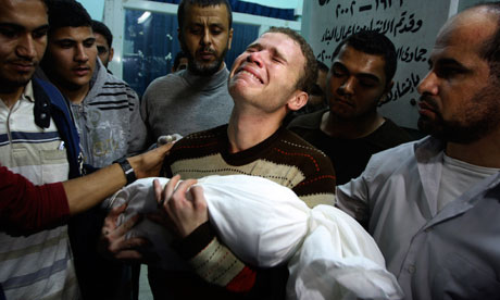 Jihad Misharawi weeps while he holds the body of his 11-month-old son